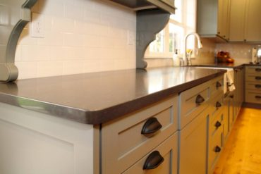 White subway tile backsplash and black cabinet hardware punctuate the custom color of the cabinets and quartz countertops. Flooring is a wide plank character white oak.