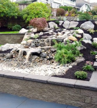 Terraced waterfall created with Columbia Granite Rockery and river rock installed by Full Throttle Landscaping