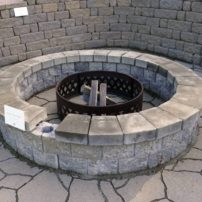 This demonstration firepit and patio area features Belgard Mega-Arbel that resembles flagstone, Allan Block Courtyard in circle pattern, and Anchor Highland stacking stone for the wall. Several similar areas onsite show possibilities for use of different high-quality stone for patios, walls and firepits.
