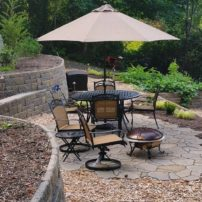A Belgard Mega-Arbel flagstone-look patio sits among curving Allan Block Europa series stacked stone walls in a landscape by Hedahl Landscape, Deck & Patio (Photo courtesy Richard Hedahl)