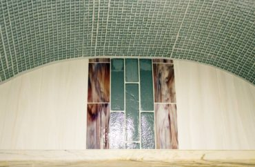 A close-up of the shower wall where it meets the barrel vault is accented with a strip of the Victoria Blue quartzite