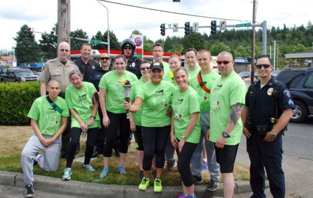 Runners and support personnel pause in East Bremerton during the Flame of Hope hand-off from the joint running team of the Kitsap County Sheriff's Office/Kitsap County Prosecuting Attorney's Office to Bremerton Police Department during the 2016 Law Enforcement Torch Run.