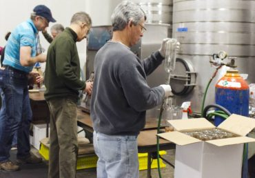 Volunteers assist in the crushing and bottling.