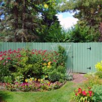 Decorative fences are an effective way to hide composting stations conveniently tucked behind gardens in the landscape.
