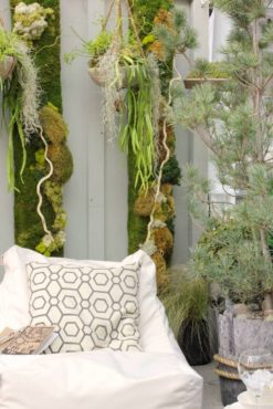 Moss art panels line the walls of the display garden flanked by hypertufa hanging baskets.