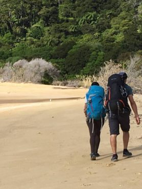 Hikers along the sand at Onetahuti Beach