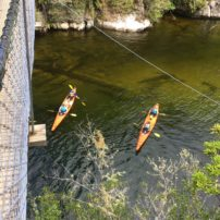 Kayaks below the suspension bridge