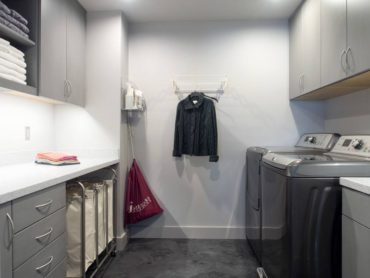 Storage is the primary focus of this second-floor laundry room — notice the catch pan peeking out under the washer.