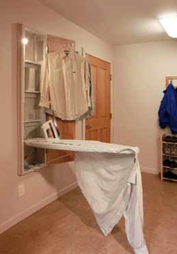 Combining laundry and mudroom amenities: built-in ironing board, coat rack and shoe rack