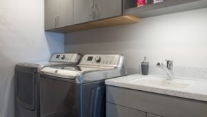 Set high to clear the washer door, these laundry room wall cabinets were made deep for accessibility.