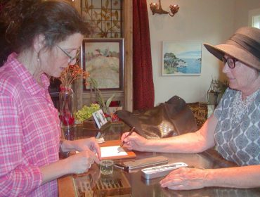 Eve Laeger, right, asks owner Annabella Serra for help with her fountain pen.