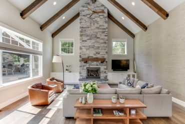 Great room grass cloth muted color scheme and textured stone fireplace (Photo by Matthew Witschonke)