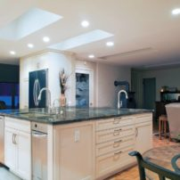 An island that bridges the kitchen and family room with two sinks, trash compactor, dishwasher and storage