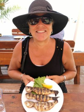 Laureen Lund enjoying grilled fish at a beachside café Burgas.