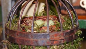 This rusty metal piece found at a vintage market inspires the use of ornate plant hangers or similar objects. Line it with moss to create a cozy space for the birds to find and build their nests.