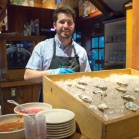 Stephen shucking oysters from Port Madison community shellfish farms
