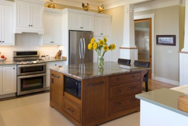 A delightful kitchen has all the amenities, including two separate farm-style sinks, a custom banquette and an abundance of work space.