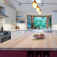 The red tile outline on the pot filler niche complements the red-painted kitchen island.
