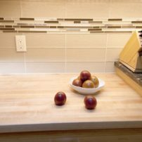 A metal-and-glass mosaic tile band intersects the textured glass tile backsplash.