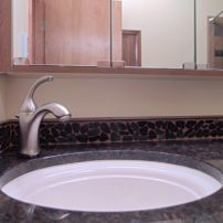 Sliced pebble tile in this vanity backsplash complements the natural stone countertop.