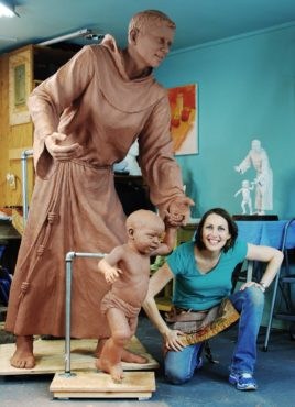 Mardie Rees stands next to the work, which was commissioned for the St. Anthony North Health Campus by the Centura Health System in Westminster, Colorado. It depicts the steadfast and wise St. Anthony guiding the young Christ Child as he takes the first steps into new discovery. In this engaging paternal moment, visitors are reminded of their own need for protection, care and comfort.