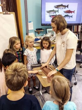 Rees teaches kids to sculpt salmon at art camp in 2017 with Harbor WildWatch.