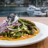 Asparagus Salad — Roasted asparagus spears served on a bed of spring greens, red onions, heirloom tomatoes, toasted almonds and goat cheese. Dressed with house-made piquillo pepper vinaigrette created by Chef John Vincent-Palacio.