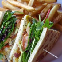 Tides Crab BLAT — Dungeness crab layered with thick sliced crispy bacon, tomato, fresh avocado and creamy Tillamook cheddar topped with wild greens. Served on toasted pita bread.