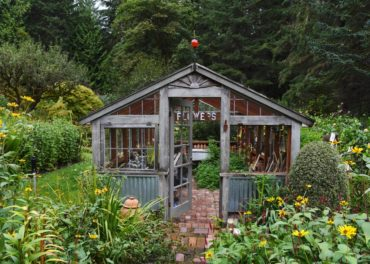The greenhouse is the center of attention among beds of cutting flowers.