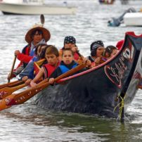 A canoe from the Hoh Tribe arrives on the shores of Point Julia, on the Port Gamble S'Klallam Reservation, during the 2012 Canoe Journey. This year, canoes will visit Port Gamble S'Klallam and Suquamish en route to the shores of the Puyallup Tribe.