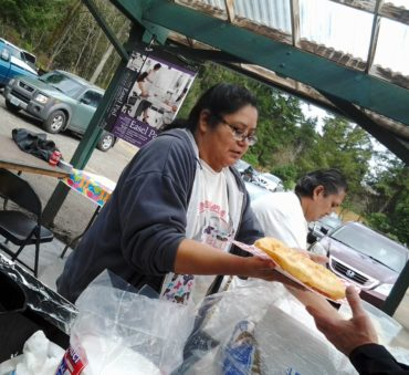 Michelle Price serves an order of frybread while her husband, John, prepares another batch of dough for frying during an event at the tribe-owned Heronswood Gardens.