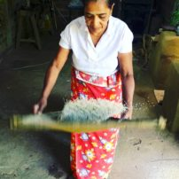 Sri Lankan woman sifts rice from the shaft.
