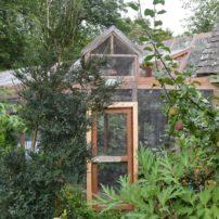 The cat enclosure nestles naturally into the garden.