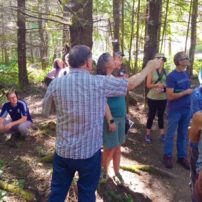 Kitsap County forester Arno Bergstrom shares forest management practices with trainees at Port Gamble Heritage Park.