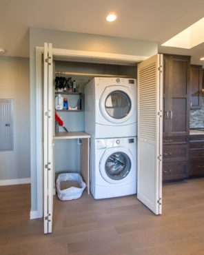 Laundry closet with hanging rod, folding counter, shelves and litter box (Photo courtesy A Kitchen That Works LLC)