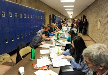 Judges scoring sheets and writing comments for students