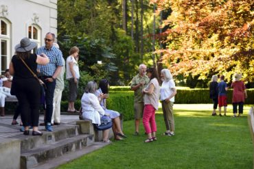"""Visitors to the residence at Bloedel enjoy an art show """"Inspired by Bloedel"""" and a sunny evening with a view of Puget Sound."""