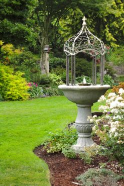 Birdbath with fountain embellished with a metal, gazebo-like structure