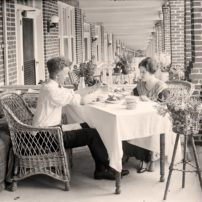 A couple dines at a table on the front porch of their row house, 1924. (Herbert A. French Collection/Library of Congress)