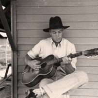 A migratory worker plays guitar on the front porch of his home in the Agua Fria Labor Camp, Arizona, May 1940. (Russell Lee/Library of Congress)