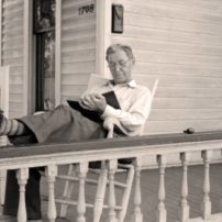 A man relaxes with a book on the front porch of his home in Vincennes, Indiana, in July 1914. (John Vachon/Library of Congress)