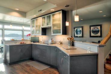 On-trend, contemporary, grey-textured laminate base cabinets combined with aluminum wall cabinet doors with frosted glass