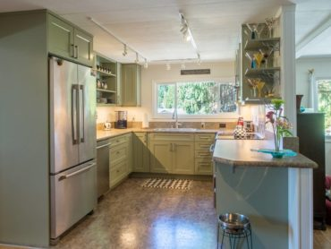 Trending, green-painted cabinets with customized open shelves for personalized decorative options