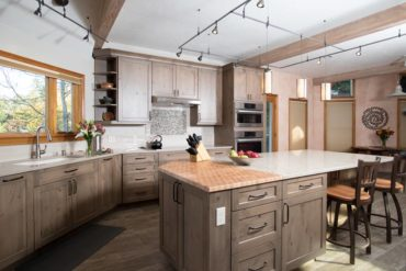 Crown molding and light valance with a complimentary profile gives this rustic kitchen a tailored look.