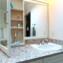 Customized bathroom storage and mirror frames matched to vanity cabinet profile