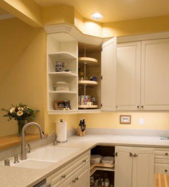 Trending, painted raised-panel -oak cabinets with corner-optimizing convenience hardware