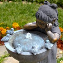 Birdbaths are always popular in a garden. This one adds a bubbling fountain for a bronze girl to gaze in fascination.
