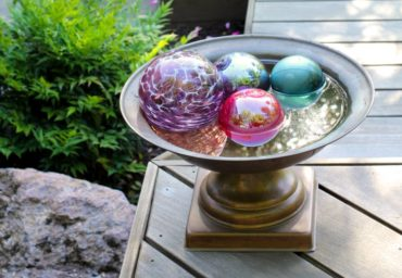 Any watertight container can quickly stand in as a water feature. Here an urn is filled with floating glass globes.