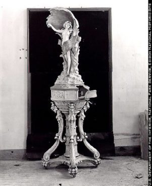 A phonograph cabinet built with Edison Portland Cement, 1912. The clockwork portion of the phonograph is concealed in the base beneath the statue; the amplifying horn is the shell behind the human figure. Today's version is the TV that can be disguised as art.