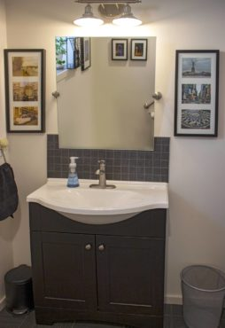 Upstairs guest bath is wheelchair-accessible, including a carved-out sink for wheelchairs and a tipable mirror with just a touch.